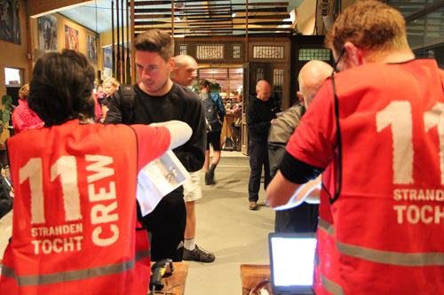 Vrijwilligers scannen e-tickets deelnemers 11strandentocht