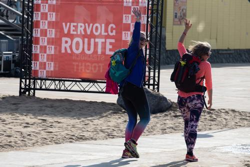 Deelnemers 11strandentocht zwaaien naar de camera in Scheveningen